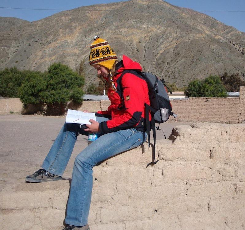 Lesend in Argentinien sitze ich auf der Mauer mit den Bergen im Hintergrund
