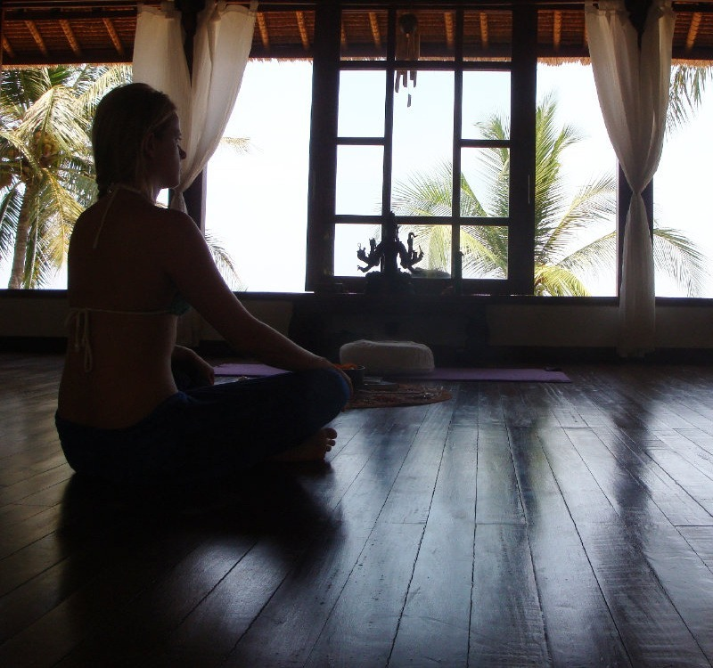 Ich meditiere auf einem Holzboden, die Luft geht durch das offene Fenster