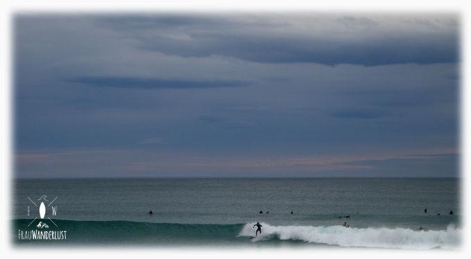 Ein Surfer surft in den Abend hinein
