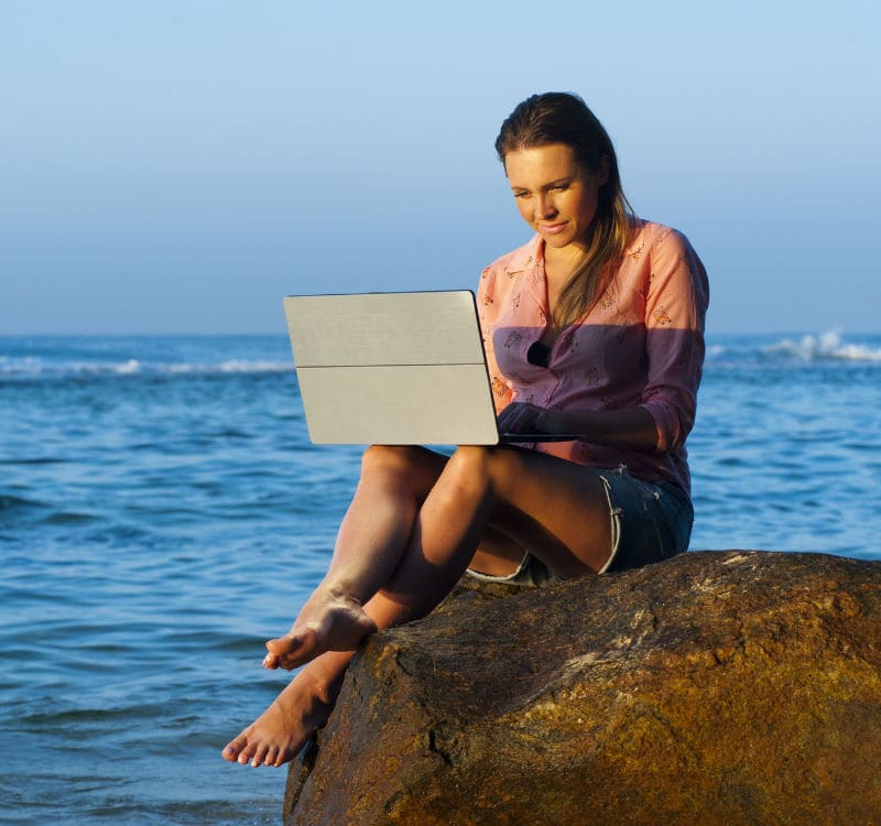 Frau arbeitet mit Laptop am Meer